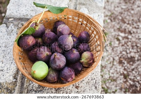Fresh figs with leaves in basket, on stone table. Natural Fruit of garden. Top view. - stock photo