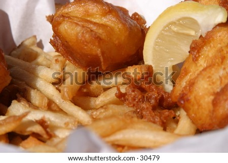 fresh fish and chips in a wicker basket with butcher paper and a lemon wedge are about to be eaten by the photographer - stock photo