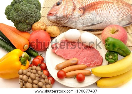Fresh fish and meat surrounded by brightly colored fruit and vegetables. - stock photo