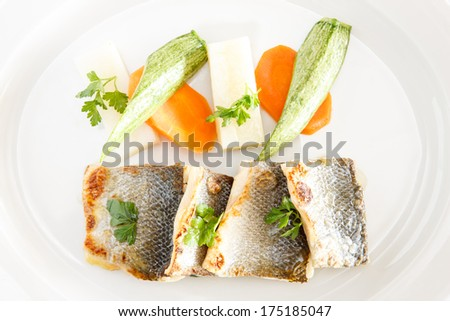 Fresh fish fillet with Pan-fried, saffron potatoes buttered vegetables, lemon and olive oil - stock photo