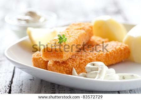 fresh fish fingers with potatoes and remoulade sauce - stock photo