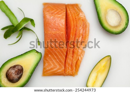 Fresh fish for sushi and avocado on white board table. Vivid colors. Healthy food. Tasty and raw food - stock photo