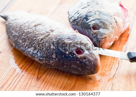 Fresh fish is cut on the kitchen table - stock photo