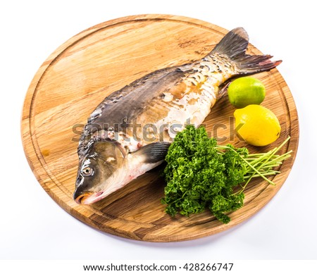 Fresh fish on a wooden board with vegetables and spices. - stock photo