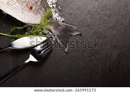 Fresh fish on crushed ice with cutlery placed with the tail visible in the corner over grey slate with copyspace - stock photo