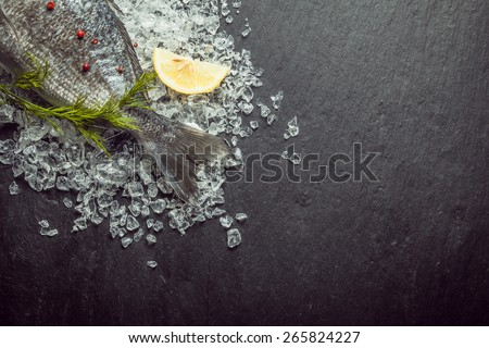 Fresh fish on crushed ice with dill displayed with the tail visible in the top left corner of the frame on a slate background with copyspace - stock photo