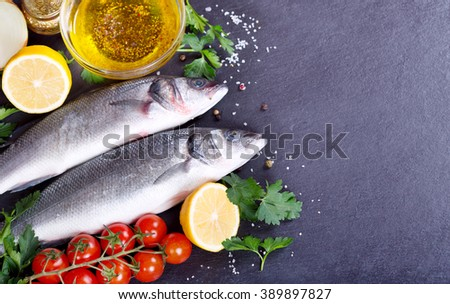 fresh fish sea bass on dark background - stock photo