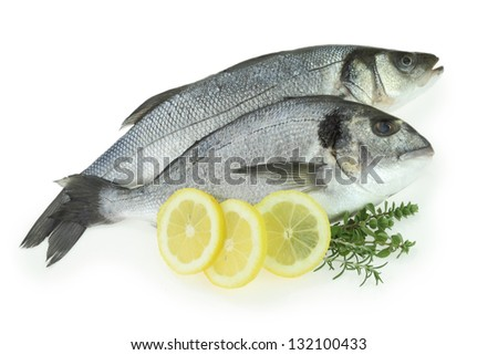 Fresh fishes with lemon and herbs isolated on white - stock photo
