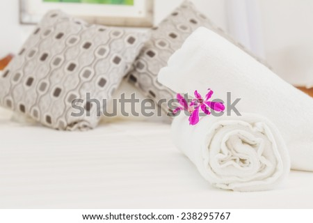 fresh flower and towel on bed, hotel room bedroom interior - stock photo