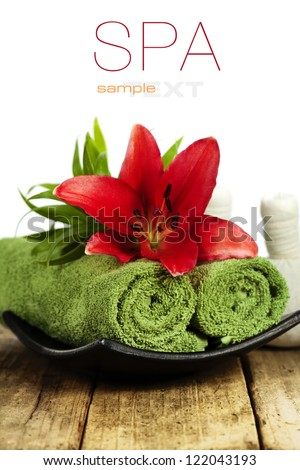 Fresh flowers, towels and Herbal massage balls on wooden surface (with easy removable sample text) - stock photo