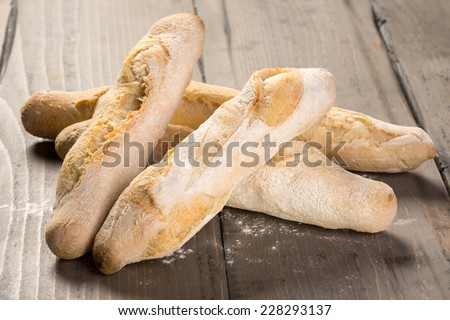 Fresh French baguette on wooden table - stock photo