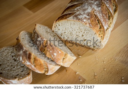 Fresh french market bread sliced on wood cutting board from top view, with both loaf and slices shown, with white background - stock photo
