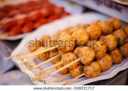Fresh fried thai no name meatballs served on a skewer. Traditional asian cuisine. - stock photo