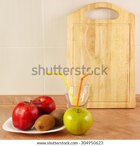 Fresh fruit and a glass of cocktail on the kitchen table - stock photo