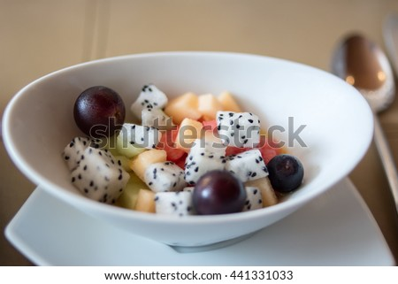Fresh Fruit : Bowl of healthy fresh fruit salad on background. Top view.  Set of breakfast fruit salad in white bowl with spoon. Close up image and natural light in summer season - stock photo