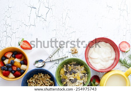 Fresh fruit salad, nuts, yogurt and granola for breakfast, close-up, top view, horizontal background, copy space - stock photo
