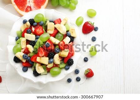 Fresh fruit salad on white wooden table - stock photo