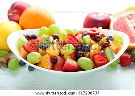 Fresh fruit salad on wooden table - stock photo