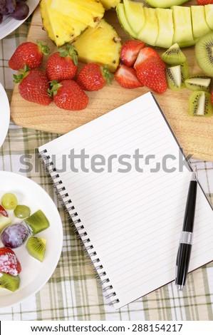 Fresh fruit salad, recipe book, copy space, vertical - stock photo