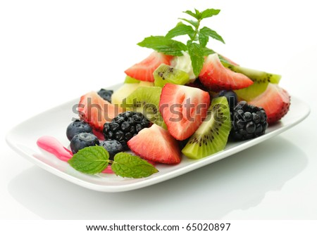 fresh fruit salad with mint in a white dish - stock photo