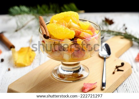 Fresh fruit salad with orange, apple, raisins, peach and cinnamon in dessert cup, close up - stock photo