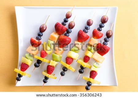 Fresh fruit shish kebabs arranged diagonally on a modern square plate for a healthy vegetarian buffet or dessert, viewed from above on a yellow summer table - stock photo