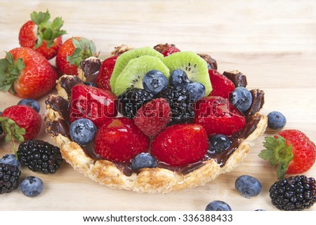 Fresh fruit tart with flower shaped pie crust sprinkled with sugar crystals coated with chocolate filled with custard topped with fresh strawberries, blue berries, boysenberries and kiwis - stock photo