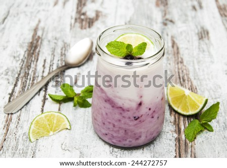 fresh fruit yogurt with blackberries and lime on a wooden background - stock photo
