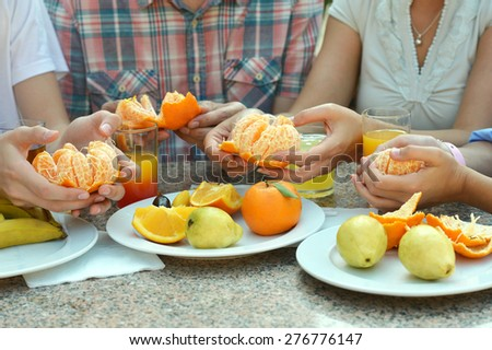 Fresh fruits and hands closeup at the table - stock photo