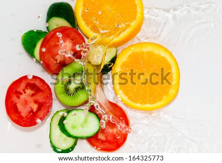 fresh fruits and vegetables in water on a white background - stock photo
