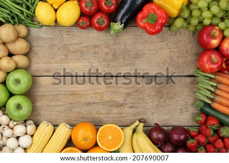 Fresh fruits and vegetables on a wooden board with copyspace - stock photo