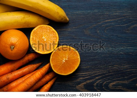 Fresh fruits and vegetables on blue wooden background with copy space - stock photo