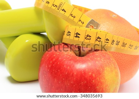 Fresh fruits, apple, grapefruit, tape measure and green dumbbells for using in fitness, concept for slimming, healthy nutrition and lifestyle - stock photo