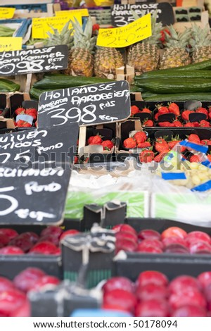 Fresh fruits at a greengrocer's stall focus on the strawberries - stock photo