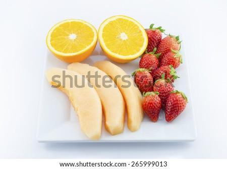 Fresh fruits in plate on white : Melon,Strawberry,Orange - stock photo