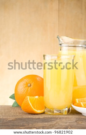 fresh fruits juice in glass and slices isolated on wood background - stock photo