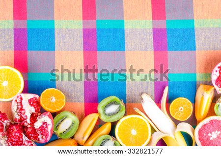 Fresh fruits on a colorful checkered kitchen towel. Raw and vegetarian eating frame. Sliced orange, persimmon, kiwi, tangerine, banana, lemon, apple,  grapefruit, pomegranate, lime,  Top view - stock photo