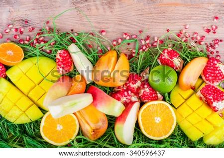 Fresh fruits on a wooden background. Raw and vegetarian eating frame. Sliced orange, persimmon, kiwi, tangerine, banana, lemon, apple,  grapefruit, pomegranate, lime, mango. Top view. Fruit set. - stock photo