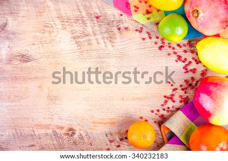 Fresh fruits on wooden background. Summer background. Raw and vegetarian eating background. Lemon, apple,  grapefruit, pomegranate, lime, persimmon, tangerine, orange, pink pepper. Top view - stock photo