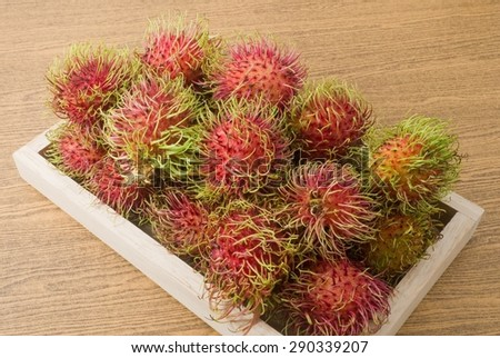 Fresh Fruits, Ripe and Sweet Refreshing Rambutan Served on A Wooden Tray. - stock photo