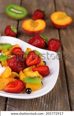 Fresh fruits salad with ice cream on plate and berries on wooden background - stock photo