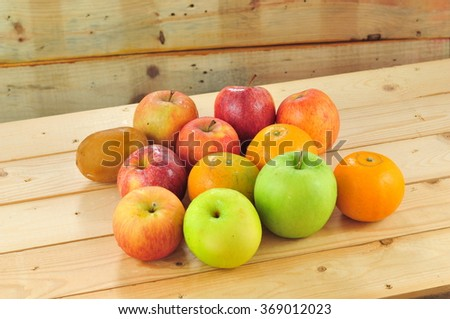 Fresh fruits such as oranges, red apples, green apples, kiwi on the table with wooden background - stock photo