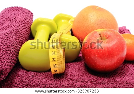Fresh fruits, tape measure and green dumbbells for using in fitness lying on purple towel, concept for slimming, healthy nutrition and lifestyle - stock photo