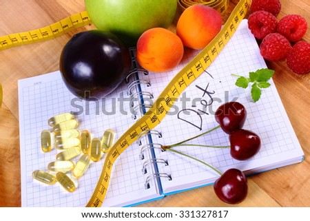 Fresh fruits, tape measure and tablets supplements on notebook for writing notes, choice between healthy eating and slimming pills - stock photo