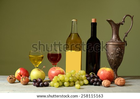 Fresh fruits, wine and metal carafe on the table - stock photo