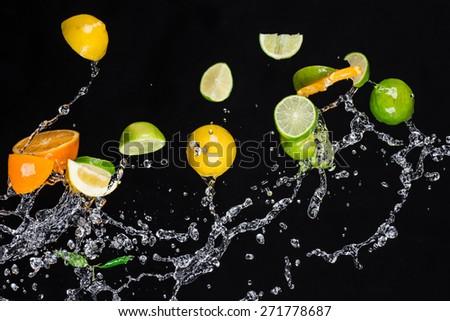 Fresh  fruits with water splash isolated on black background - stock photo
