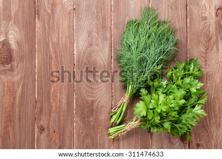 Fresh garden dill and parsley herbs on wooden table. Top view with copy space - stock photo