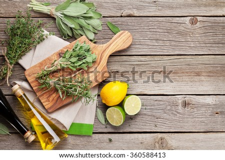 Fresh garden herbs and condiments on wooden table. Top view with copy space - stock photo