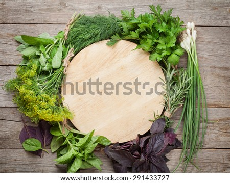 Fresh garden herbs and cutting board over wooden table. Top view with copy space - stock photo