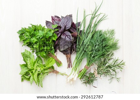 Fresh garden herbs over wooden table. Top view - stock photo
